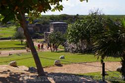 Tourists walk along a path at the Tulum Mayan Ruins.jpg